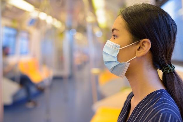 Vista di profilo della giovane imprenditrice asiatica con maschera per la protezione dallo scoppio del virus corona all'interno del treno