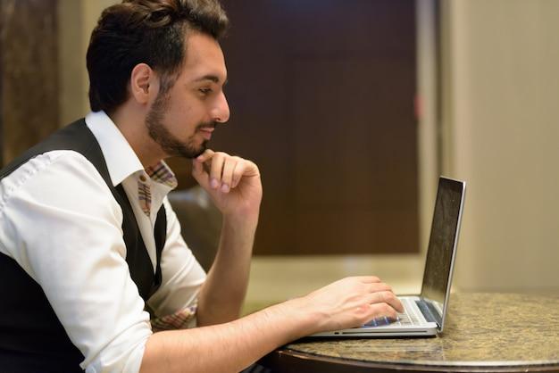 Vista di profilo del giovane uomo indiano bello pensare mentre si utilizza il computer portatile nella hall dell'hotel