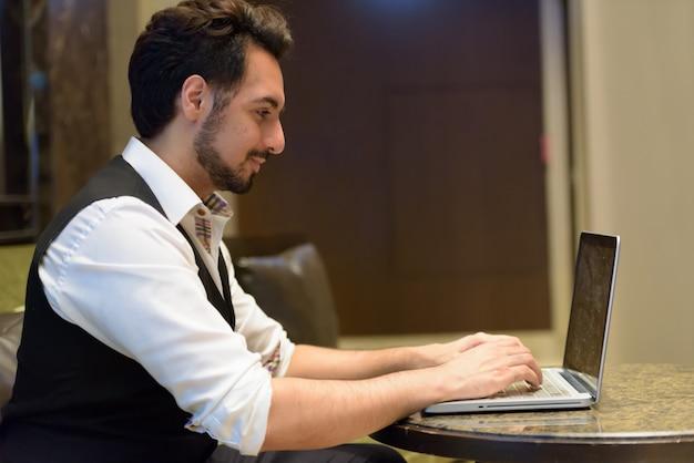 Vista di profilo di giovane uomo indiano bello utilizzando il computer portatile nella hall dell'hotel