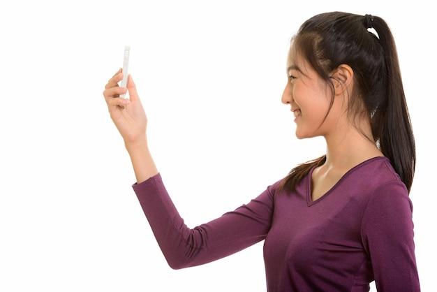 Vista di profilo di giovane adolescente asiatico felice sorridente