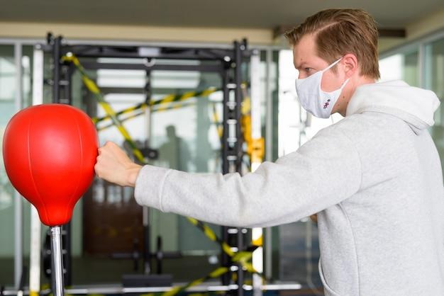 Vista di profilo del giovane uomo che indossa la maschera e boxe in palestra