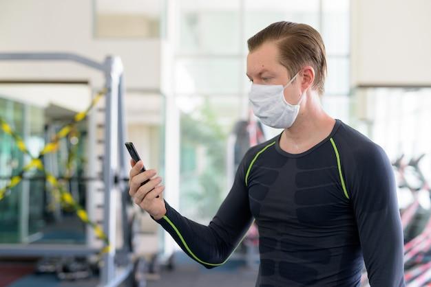Vista di profilo di un giovane uomo con maschera utilizzando il telefono in palestra durante il coronavirus covid-19