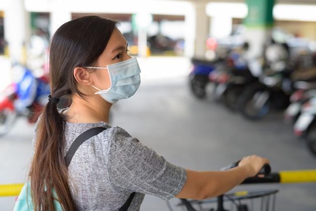 Vista di profilo della giovane donna con la maschera tenendo la bicicletta