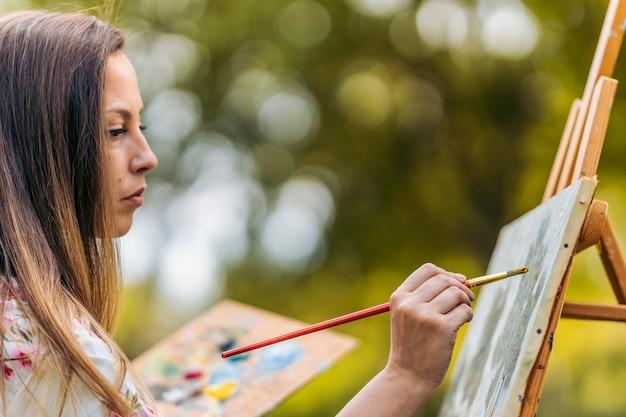 Profilo di una donna che dipinge circondata da alberi in un parco.