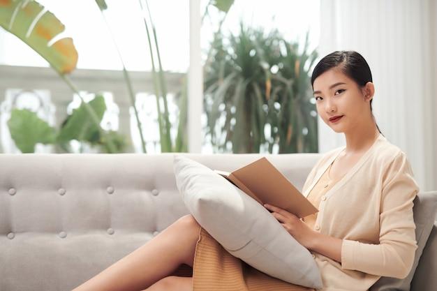 Profilo di giovane donna asiatica che si rilassa sul divano e legge un romanzo a casa