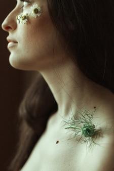 Profilo di una giovane bruna con piccole margherite sulle guance e uno stelo verde sulla clavicola.