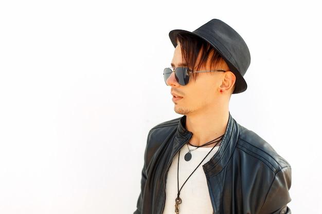 Profilo di un giovane uomo bello con cappello da sole in giacca nera su sfondo bianco