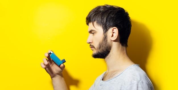 Profilo giovane uomo malato, tenendo inalatore asmatico sulla parete gialla.