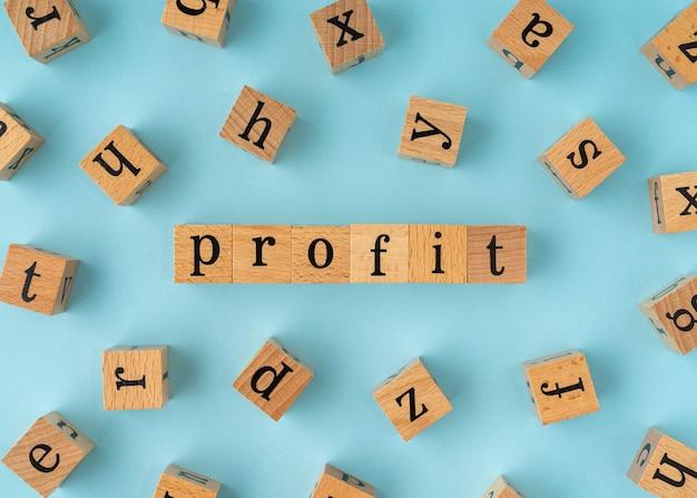 Parola di profitto sul blocco di legno. vista piatta su sfondo blu.