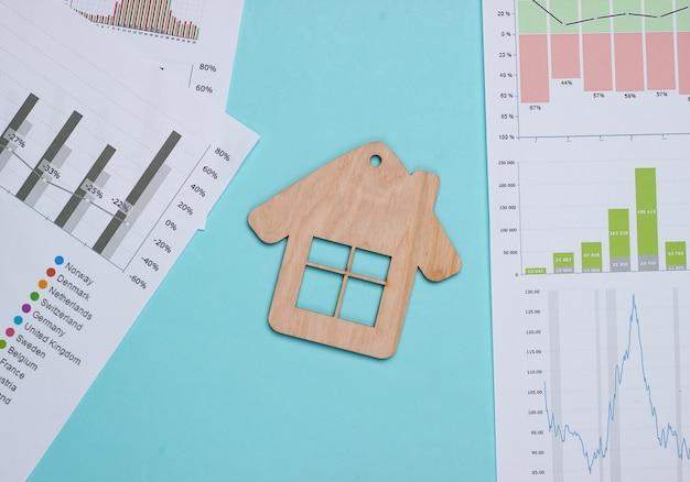 Investimento redditizio. analisi di mercato. acquistare una proprietà. minifigure di casa, grafici e chartc su sfondo blu pastello