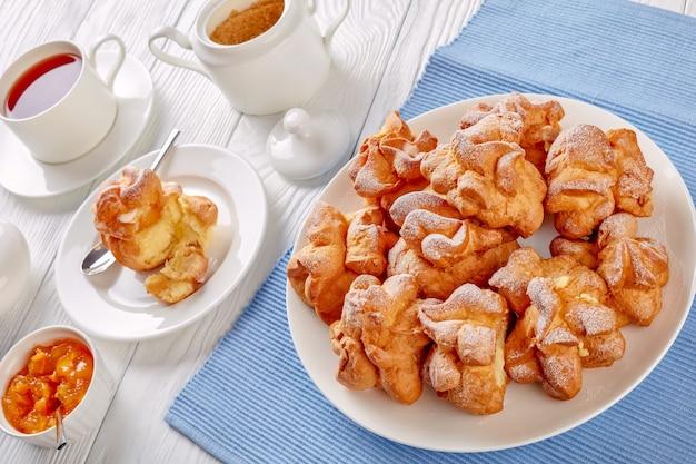 Profiterole o eclair. profiterole con crema pasticcera ripieno servito per colazione su un piatto bianco con tè e marmellata di albicocche in una ciotola su un tavolo di legno, vista orizzontale dall'alto, close-up