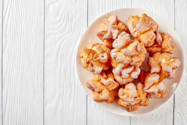 Profiterole condito con zucchero a velo con ripieno di crema pasticcera su un piatto bianco su un tavolo di legno, vista orizzontale dall'alto, close-up, flatlay. copia spazio
