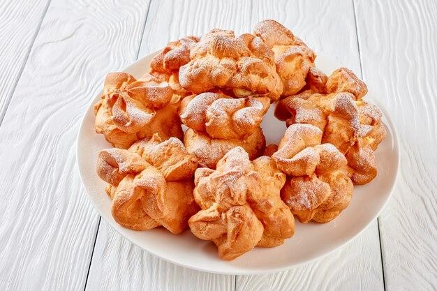 Profiterole condita con zucchero a velo con crema pasticcera ripieno su un piatto bianco su un tavolo di legno, vista orizzontale dall'alto, close-up