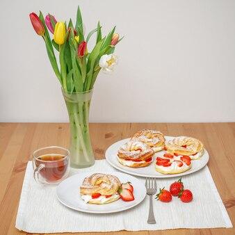 Profiteroles o torte di pasta sfoglia con panna montata e fragole, servite in tavola con fiori di tulipano