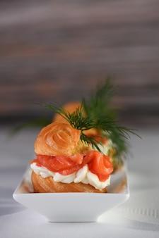 Profiteroles ripieni di crema di formaggio e salmone, decorati con un rametto di aneto. avvicinamento