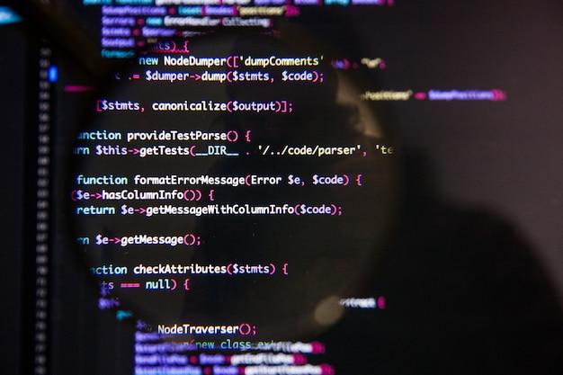 Programma concetto di visualizzazione del codice illustrativo sullo schermo attraverso la lente di ingrandimento
