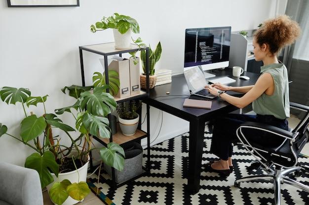 Programmatore seduto sul suo posto di lavoro e lavorando con il software sul laptop
