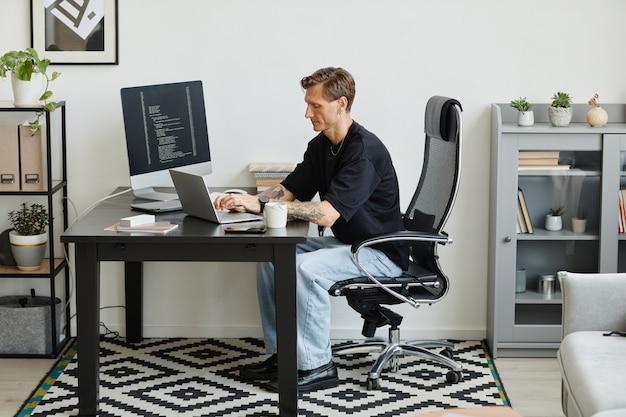 Programmatore seduto al suo posto di lavoro e lavorando sul laptop che sviluppa un nuovo software