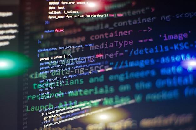 Programmatore che lavora in un ufficio aziendale di sviluppo software. dati binari digitali sullo schermo del computer. lavoro di digitazione di script per computer. schermata astratta del codice di programmazione dello sviluppatore di software.