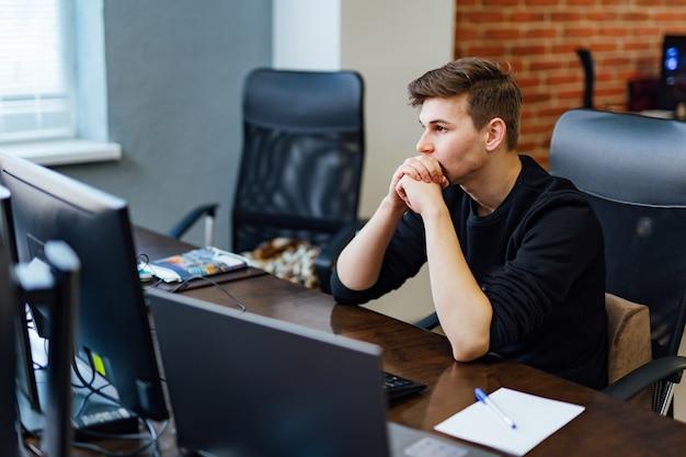 Programmatore che lavora in un ufficio di una società di sviluppo software. uomo premuroso. progettazione del sito web.