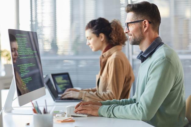 I programmatori che digitano il codice di dati che lavorano al progetto nella società di sviluppo di software