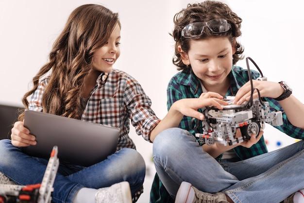 Dispositivi di programmazione insieme. bambini curiosi, utili e attivi, seduti a casa e utilizzano gadget e dispositivi mentre esprimono interesse