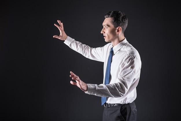 Progresso e innovazione. piacevole simpatico uomo emotivo in piedi davanti allo schermo digitale e muove le mani mentre prova la nuova tecnologia