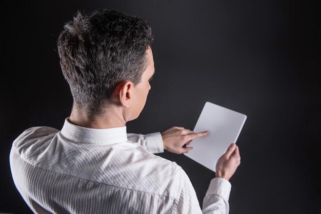 Dispositivo progressivo. vista dall'alto di un tablet moderno nelle mani di un uomo adulto intelligente e simpatico