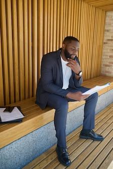 Documentazione del progetto. un uomo d'affari in giacca e cravatta seduto su una panchina con documenti per l'analisi in mano