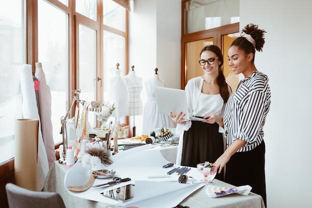 Il project manager consulta il giovane designer due donne nello studio di design