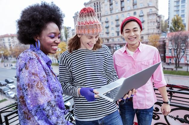 Progetto insieme. tre freelance allegri raggianti alla moda che lavorano insieme al progetto