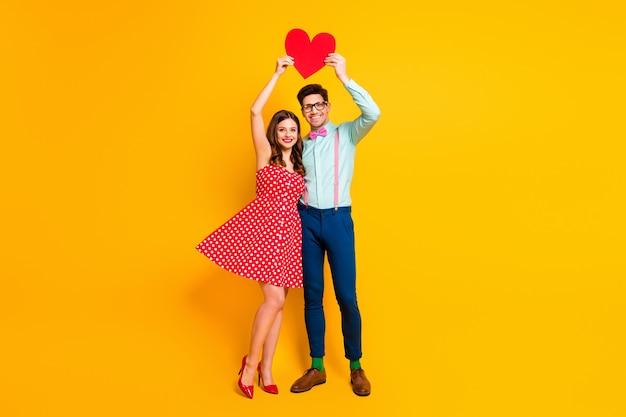 La coppia del ballo di fine anno si abbraccia alzando un grande cuore di carta
