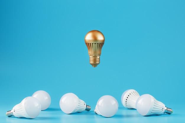 Una prominente lampadina d'oro levita sopra un ambiente di lampadine a led bianchi.