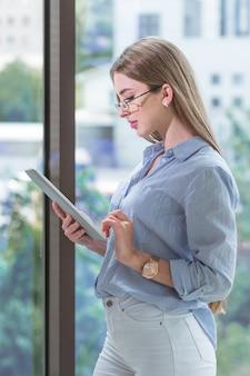 Il giovane e promettente impiegato moderno sta lavorando su un tablet vicino alla finestra