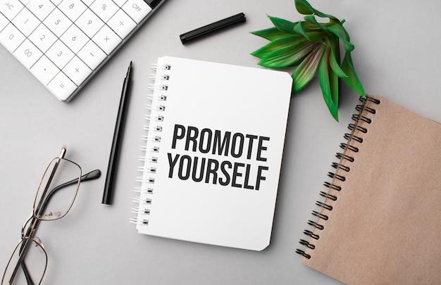 Promuovi te stesso è scritto in un quaderno bianco con calcolatrice, taccuino colorato, pianta, pennarello nero e occhiali.