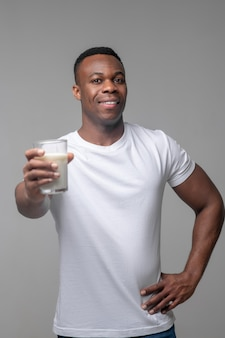 Nutrizione appropriata. allegro giovane bell'uomo dalla pelle scura che porge un bicchiere di latte in avanti di ottimo umore