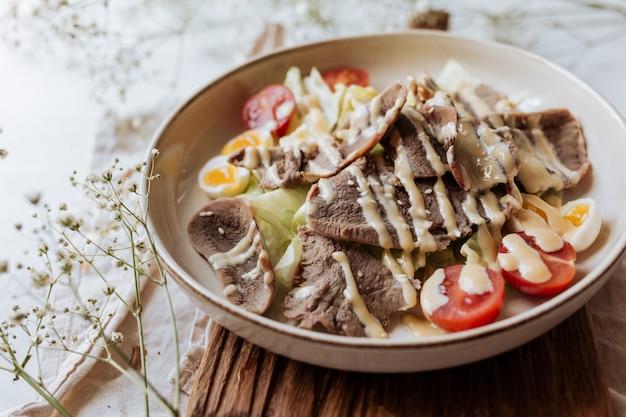 Insalata corretta di carne e verdure bollite, versata con salsa di maionese fatta in casa