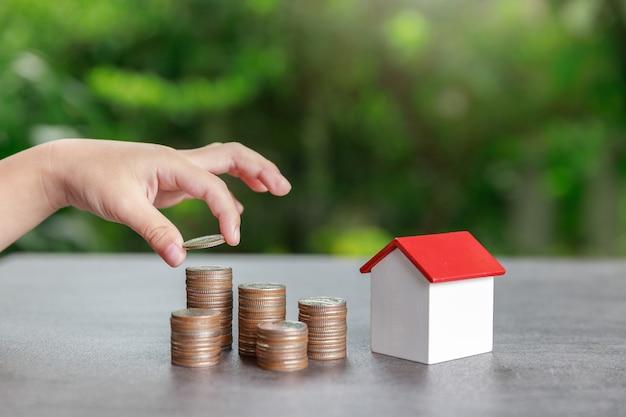 Investimento immobiliare e concetto finanziario di ipoteca della casa, ragazzo asiatico che mette i soldi alla pila della moneta con il modello della casa su fondo verde.