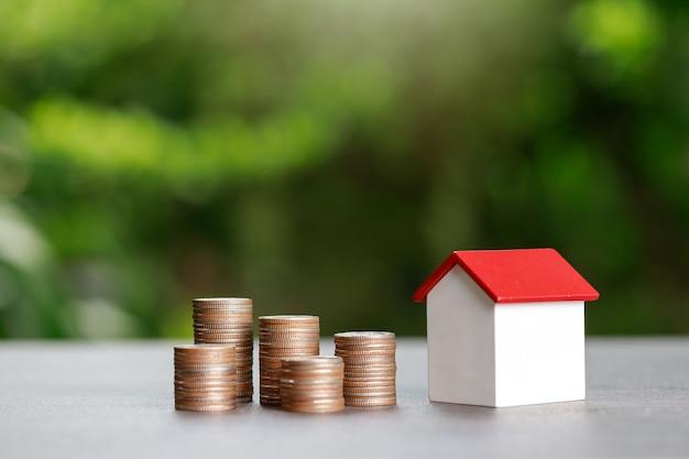 Investimento immobiliare e concetto finanziario mutuo casa, pila di monete con modello di casa su sfondo verde.