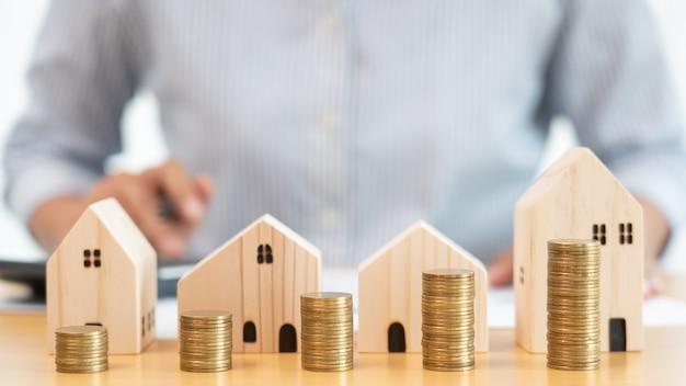 Investimento immobiliare e concetto finanziario mutuo casa, mano di un uomo d'affari che sta impilando monete per investimenti immobiliari, risparmiando per l'acquisto di abitazioni o speculazioni.