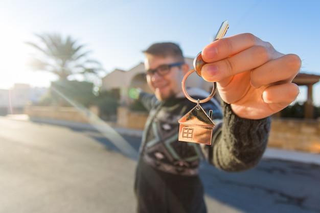 Proprietà della proprietà nuova casa e concetto di persone allegro giovane che tiene la chiave di casa