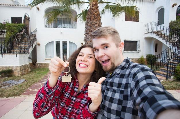 Concetto di proprietà, immobiliare e appartamento - giovani coppie divertenti felici che mostrano le chiavi della loro nuova casa.