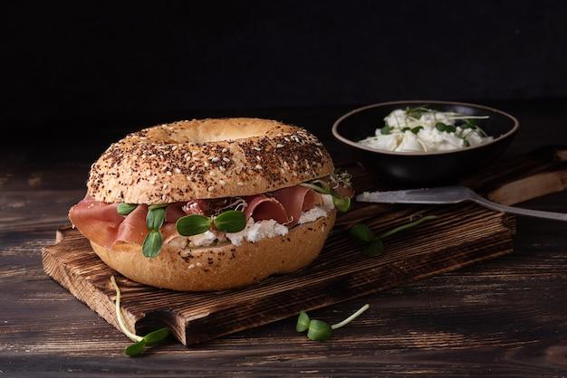Panino prosciutto e formaggio, tagliere con bagel prosciutto e ricotta su fondo in legno scuro, stile rustico.