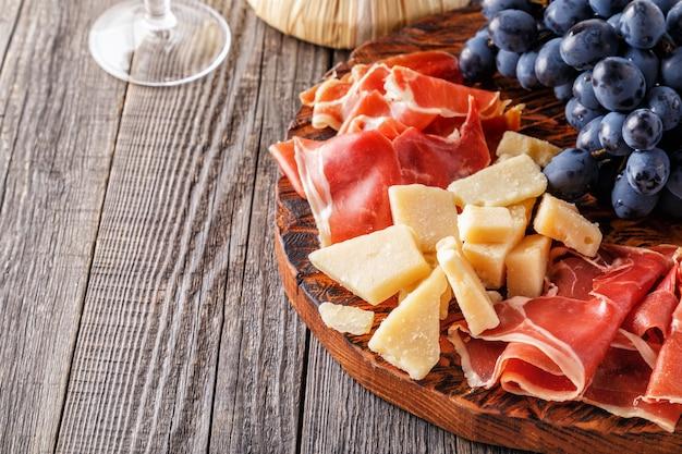 Prosciutto, vino, uva, parmigiano sul tavolo di legno.