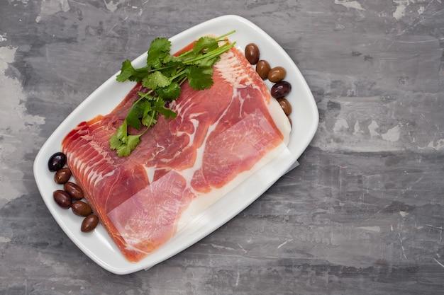 Prosciutto con olive e prezzemolo sul piatto bianco sulla superficie in ceramica