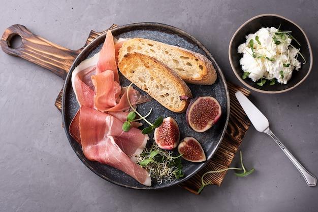 Prosciutto con fette di pane e fichi su un piatto su uno sfondo di cemento, antipasto italiano con crema di formaggio, primo piano.