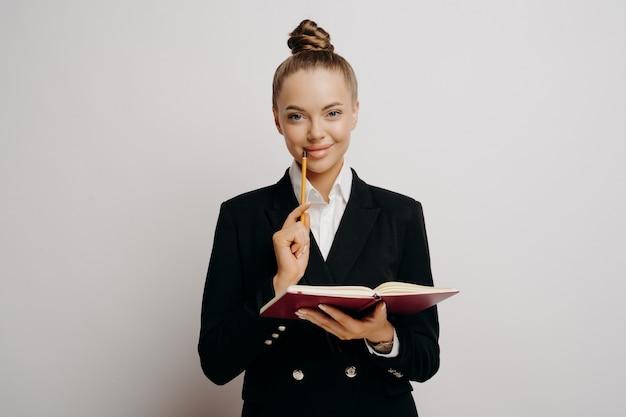 Prospettiva dirigente femminile in abito scuro con i capelli in una crocchia che tiene il taccuino pensando a nuove idee e scrivendole con la matita sul labbro, guardando dritto in avanti, isolato su sfondo grigio