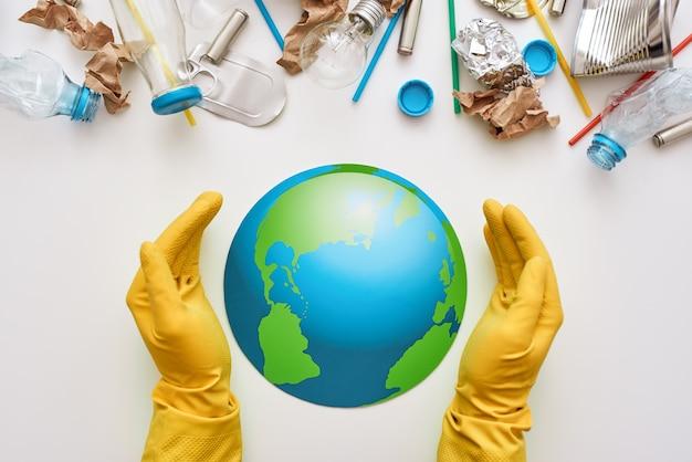 Proteggi l'ecologia del mondo. le mani umane in guanti hanno protetto il globo. plastica, lattine, rifiuti di carta sono mescolati insieme