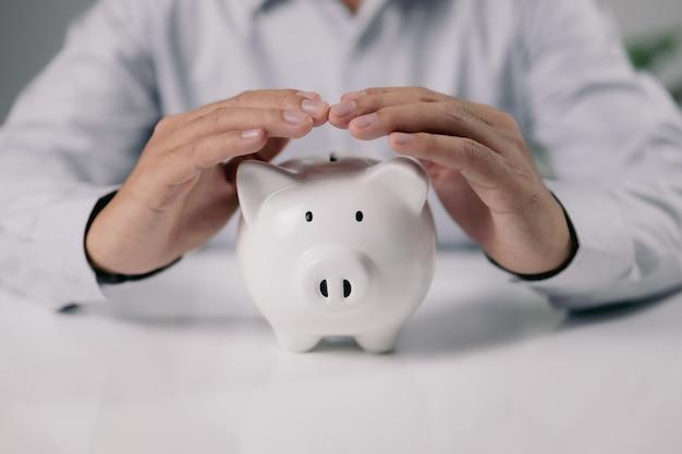 Proteggi i tuoi soldi, la mano dell'uomo protegge il salvadanaio sul tavolo bianco. risparmia denaro e investimenti finanziari
