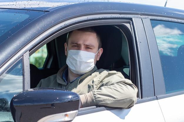 Proteggiti dal coronavirus con una maschera mentre guidi un guidatore mascherato in un'auto argentata
